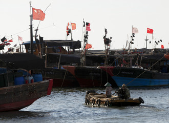 A dinghy ferries people to fishing boats at a port in the city of Dongfang on the western side of China's palm-fringed island province of Hainan