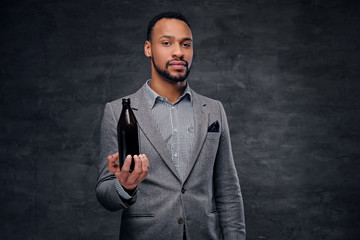 Portrait of stylish black male dressed in a grey suit holds a craft beer bottle.