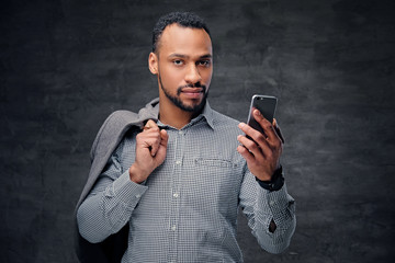 Casually dressed black American male holds smart phone.