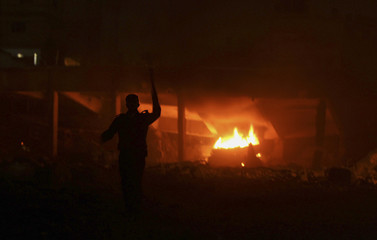 A Palestinian Hamas policeman tries to douse a fire after Israeli aircrafts hit Hamas security sites in Gaza City