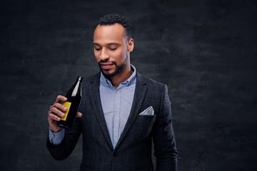 Portrait of elegant black male dressed in a suit tasting craft beer.