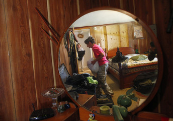 Kathy McMichael moves her possessions in the bedroom of her home in anticipation of flooding in Butte LaRose, Louisiana