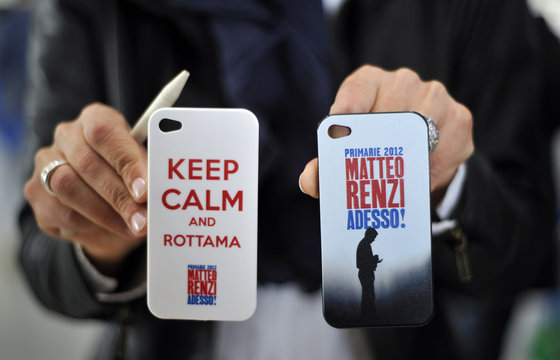 A staff member shows mobile device covers with designs in support of Democratic Party member and Mayor of Florence Matteo Renzi in Turin