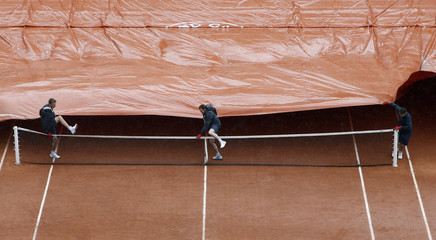 Workers pull a tarp over court Suzanne Lenglen as rain interrupts a men's single match between Pavic of Croatia and Simon of France at the French Open tennis tournament at the Roland Garros stadium in Paris