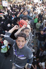 Boys shout slogans while sitting on a wooden wall separating men and women at Taghyeer (Change) Square, during a demonstration to demand the trial of Yemen's outgoing President Ali Abdullah Saleh in Sanaa