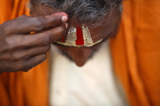 A Hindu holy man or sadhu looks into the mirror (unseen) as he applies tika on his forehead at the premises of Pashupatinath Temple in Kathmandu