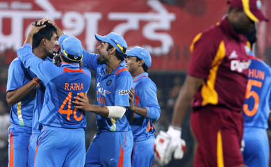 India's Sharma is congratulated after taking the wicket of West Indies' Pollard during their cricket match in Indore