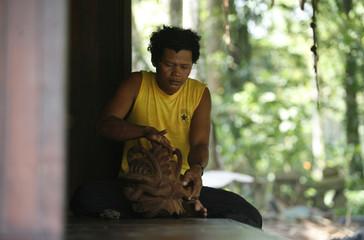 Mah Meri man works on his wood carving at his workshop in the Mah Meri tribe village of Sungai Bumbun on Carey Island, outside Kuala Lumpur