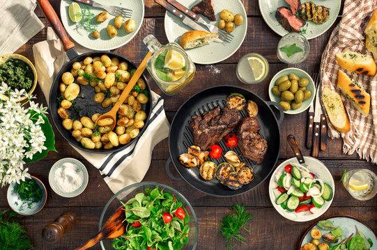 Dinner table with meat grill, roast new potatoes, different food