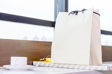 White paper shopping bag and gift placed on table near the window.
