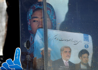 A supporter of Afghan presidential candidate Abdullah looks out of a car window after an election rally in Mazar-I-Shariff