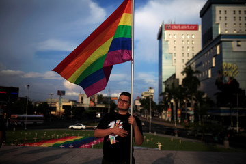 A member of the LGBT community participate in a vigil in memory of the victims of the Orlando Pulse gay nightclub shooting and hate crimes in San Salvador