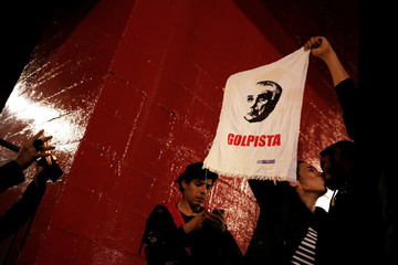 """Demonstrator takes a picture of a couple kissing as they hold a cleaning wipe with the image of  Brazil's President Temer reading """"Coup monger"""" during a protest against him in Sao Paulo"""
