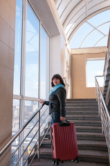 Woman with a suitcase on the stairs of station