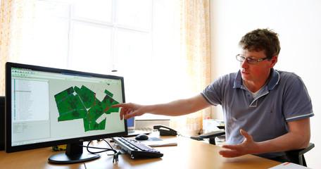 "Schwarzensteiner, factory manager of ""Poschinger Bray'sche Gueterverwaltung"", explains the 'talking fields' biomass map on a computer in Irlbach"