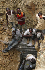 Workers look up from one of the pits of a mine, believed to contain gold, in Minna