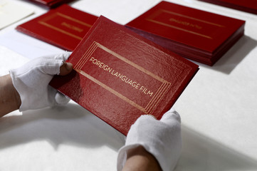 A worker assembles envelopes and announcement award cards bearing the names of Oscar winners for the 87th Academy Awards in Los Angeles