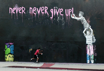 A boy skateboards past a mural in Los Angeles