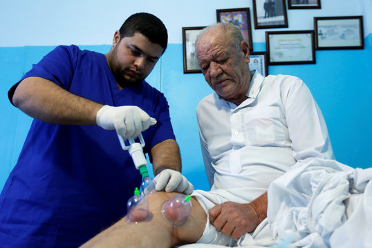 Yaseen Khdayrat, a general medicine doctor specializing in alternative medicine, puts the cups on his patient Abu Alaa's leg during a cupping session in the city of Zarqa