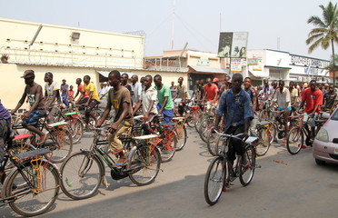 Residents cycle as they participate in a demonstration against the Rwandan government in Burundi's capital Bujumbura