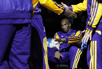 Los Angeles Lakers Kobe Bryant reaches his hand out to teammates as the Lakers are announced before the start of the first half of their NBA basketball game against the Boston Celtics at TD Garden in Boston