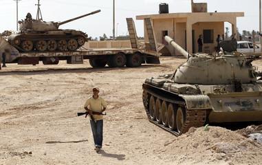 A rebel fighter walks between T-55 tanks in Misrata