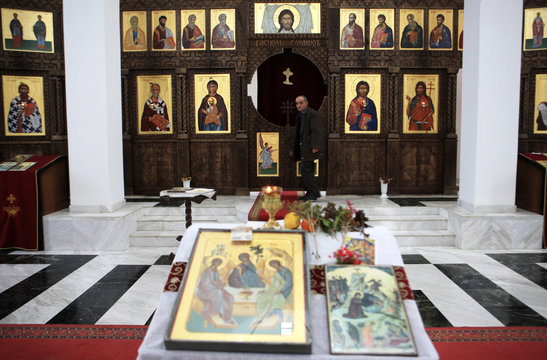 A local Kosovo Serb walks past religious icons in a church during Orthodox Christmas celebrations, in Partes
