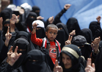 A boy and female anti-government protestors shout slogans during a demonstration to demand for the resignation of Yemen's President Ali Abdullah Saleh, outside Sanaa University