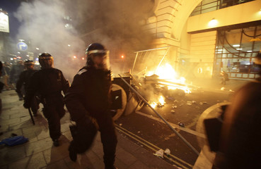 Police officers walk past burning debris after a protest in central London