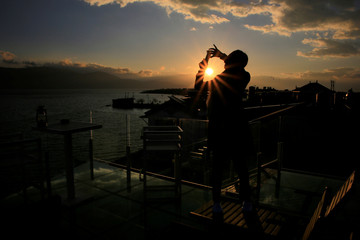 A visitor takes a video of sunrise in Erhai lake in Dali