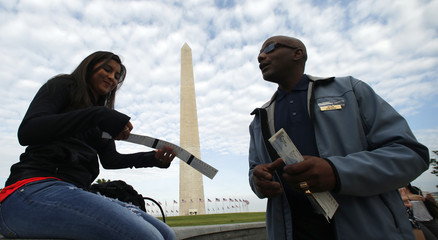 A woman receives tickets from a National Park worker for the re-opening of the Washington Monument in Washington