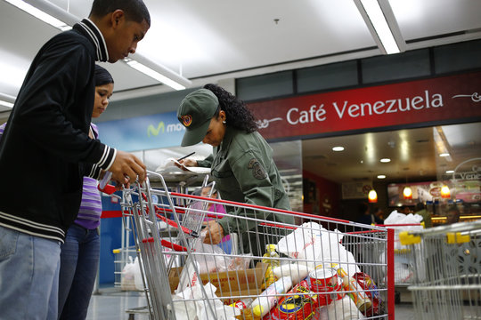 An army reservist checks a list of items purchased as people leave with their shopping at a state-run Bicentenario supermarket in Caracas
