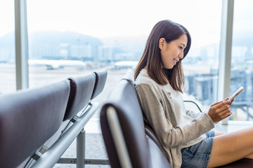 Woman working on mobile phone in airport