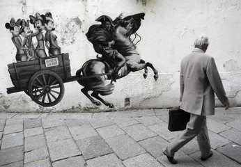 A man walks past a wallpaper depicting Italy's Prime Minister Silvio Berlusconi as Napoleon mounted on a horse in downtown Milan