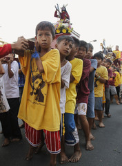 Devotees carry replica statues of Jesus of the Black Nazarene during a procession along a street in Manila
