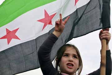 Syrian girl living in Jordan holds a Syrian opposition flag during a protest against Syria's President al-Assad in Amman