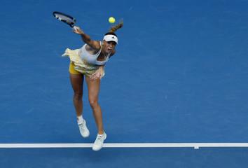 Caroline Wozniacki of Denmark serves to Garbine Muguruza of Spain during their women's singles match at the Australian Open 2014 tennis tournament in Melbourne