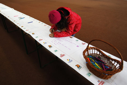 A child writes Christmas wishes on world's longest letter addressed to Santa Claus during a Guinness World Record attempt in Pantelimon