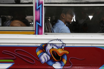 A graffiti of a cartoon character is seen on a Diablo Rojo bus as passengers look on in Panama City