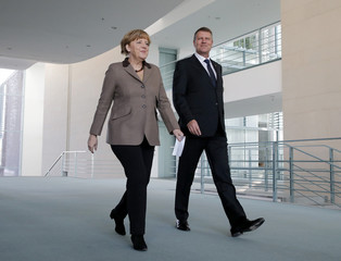 Romanian President  Iohannis and German Chancellor Merkel arrive for news conference in Berlin