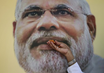 A supporter of Bharatiya Janata Party (BJP) poses with the sweets in front of the portrait of Indian Prime Minister Narendra Modi, as he celebrates after learning of initial poll results outside the party office in Mumbai
