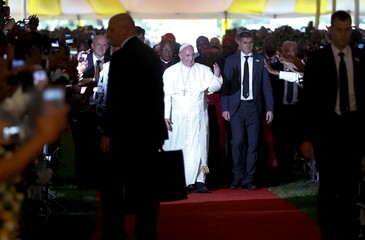 Pope Francis waves as he arrives to attend a meeting with clergy at St Mary's School in Kenya's capital Nairobi