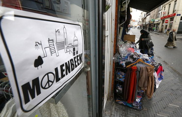 """A placard reading Molenbeek with a """"peace and love sign"""" is seen in a shopping street in the suburb of Molenbeek"""