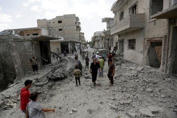 People inspect damage at site hit by airstrikes in rebel-controlled area of Maaret al-Numan town in Idlib province