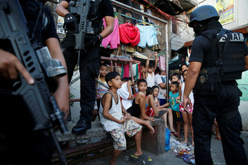 Members of Philippine National Police SWAT team stand guard near residents during an anti-drugs operation, in Pasig, Metro Manila