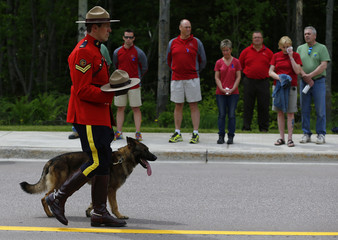A Royal Canadian Mounted Police officer walks with the hat and dog of K-9 officer David Ross, who was killed last week along with two other RCMP officers, before their funeral in Moncton