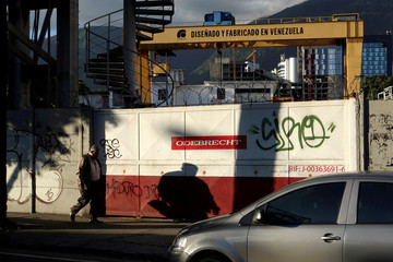 "A man walks past corporate logo of Odebrecht in a construction site with a text in a structure that reads ""Designed and made in venezuela"" in Caracas"