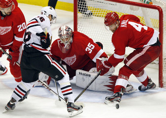 Detroit Red Wings goalie Jimmy Howard and defenseman Jakub Kindl stop Chicago Blackhawks center Marcus Kruger from scoring in the 3rd period of Game 4 of their NHL Western Conference semi-finals hockey playoff game in Detroit