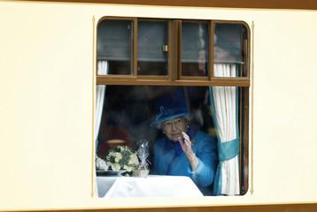 Britain's Queen Elizabeth waves as she sits aboard a train drawn by a steam locomotive at Edinburgh Waverley Station in Scotland