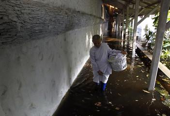 A Buddhist nun walks through floodwaters at the Sathira-Dhammasathan Buddhist meditation centre in Bangkok